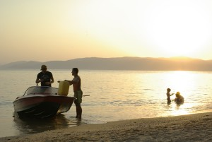 Boat Boys refueling their speed boat on the beach at sunset, Skiathos, Greece. The correct exposure.