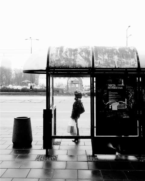 Back lit girl at bus stop in Warsaw, Poland. By Damien Demolder