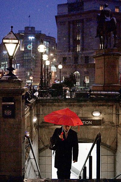 Red umbrella in the rain, London. By Damien Demolder