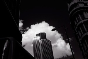 An infrared picture of Tower 42 with white clouds and a black sky